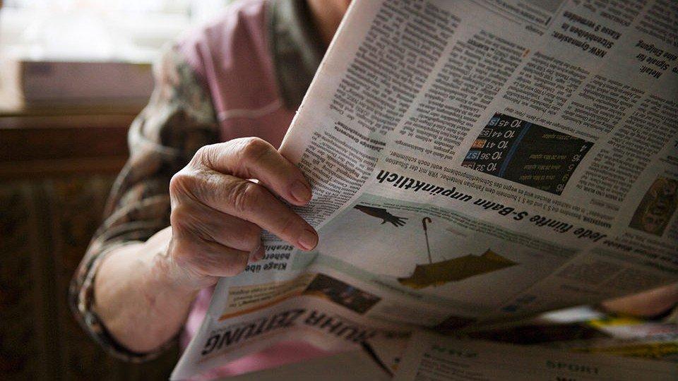 Ältere Frau liest Zeitung verkehrt herum