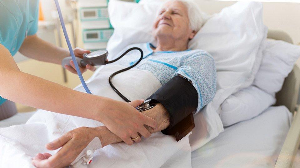 Patientin mit Schmerzen: Behandlungssituation im Krankenhaus.